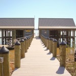 Government project: VCU Rice Center Boathouses, pier and floating dock, designed especially for the James River. Six covered boat slips with lifts, 150' of synthetic decking, 600 sf of synthetic roofing, floating dock with gangway, capped pilings with elec.